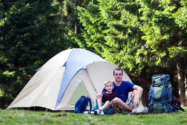 Camping wakacje. ojciec i jego syn odpoczywają w pobliżu namiotu po pieszych wędrówkach w lesie podróżowanie i zajęcia na świeżym powietrzu. szczęśliwe relacje rodzinne i zdrowy styl życia.