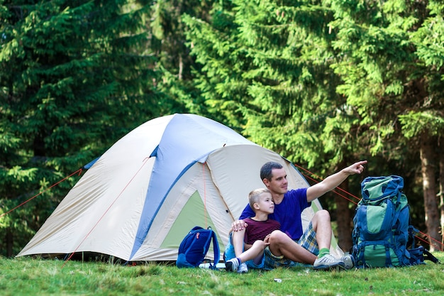 Camping wakacje. ojciec pokazuje synowi coś na odległość, odpoczywając w pobliżu namiotu po pieszych wędrówkach w lesie podróżowanie i zajęcia na świeżym powietrzu. szczęśliwe relacje rodzinne i zdrowy styl życia.