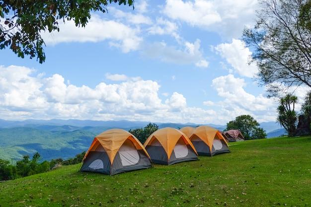Campingowi namioty w wierzchołku góra z niebieskim niebem i chmurami