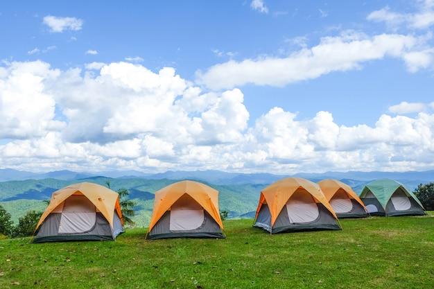 Campingowi namioty w wierzchołku góra z niebieskim niebem i chmurami.