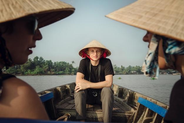 Can tho, wietnam - 02 kwietnia 2016: turysta w wietnamskim kapeluszu wybiera się na wycieczkę łodzią po delcie mekongu. grupa turystów udających się na pływający targ cai rang, popularne miejsce turystyczne w pobliżu can tho