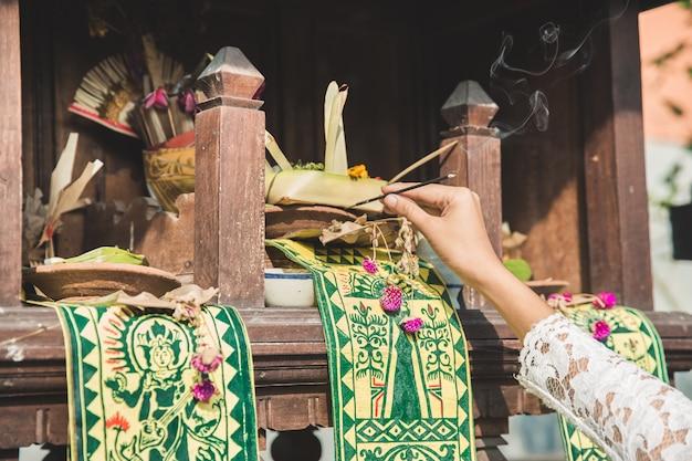 Canang sari z kadzidłem na świątyni