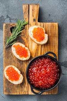 Canape tosty z czerwonym kawiorem, na szarym tle, widok z góry na płasko