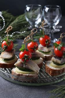 Canape z solonym śledziem, ogórkiem, gotowanymi ziemniakami, pomidorkami cherry i czarnymi oliwkami na żytnich grzankach na szarym tle. format pionowy