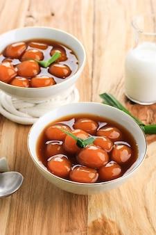 Candil oe jenang grendul to tradycyjny słodki deser owsianki z indonezji. wykonane z lepkiej kulki ryżowej o okrągłym kształcie. podawany z syropem z cukru palmowego i mlekiem kokosowym