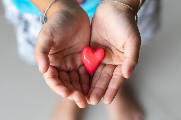 Candy czerwone serce w ręku chłopca.