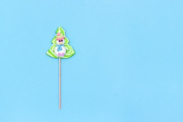 Candy lollipop zabawny bałwana i choinki na niebieskim tle.