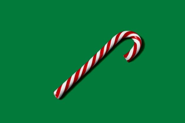 Candy trzciny paski w boże narodzenie kolory na zielonym tle.