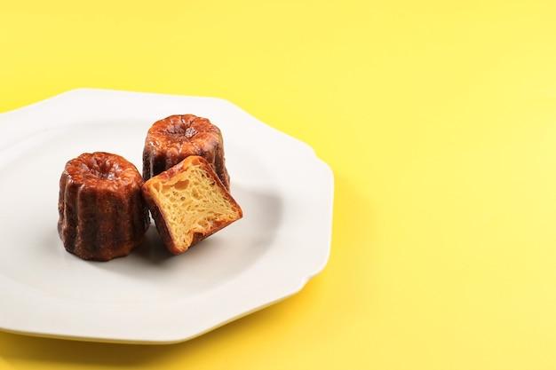 Canele classic francuskie ciasto bordeaux na szarym talerzu, na białym tle żółte tło z miejscem na kopię tekstu lub przepis