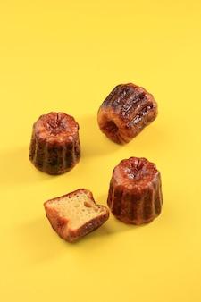 Canele lub cannele, ciasto francuskie z bordeaux. aromaty rumu i wanilii z delikatnym środkiem budyniowym i grubą karmelizowaną skórką. na białym tle na żółtym tle, selektywne ustawianie ostrości