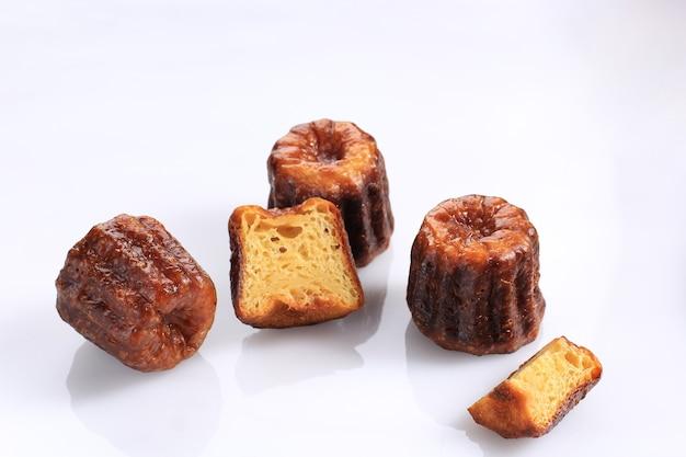 Canele lub cannele, ciasto francuskie z bordeaux. aromaty rumu i wanilii z delikatnym środkiem budyniowym i grubą karmelizowaną skórką. na białym tle, selektywne ustawianie ostrości