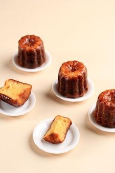 Canele lub cannele, ciasto francuskie z bordeaux. aromaty rumu i wanilii z delikatnym środkiem budyniowym i grubą karmelizowaną skórką. podawane na mini talerzu, czarne tło z miejscem na kopię