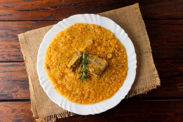 Canjiquinha to tradycyjne danie kuchni brazylijskiej z żeberkami wieprzowymi i kruszoną kukurydzą, w ceramicznym talerzu na rustykalnym drewnianym stole. zamknąć widok