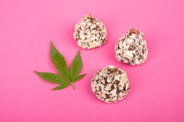 Cannabis słodycze cukierki czekoladowe truflowe z orzechami i zielonymi liśćmi marihuany na różowym tle.