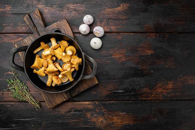 Cantharellus cibarius, zestaw grzybów kurkowych, na żeliwnej patelni, na starym ciemnym tle drewnianego stołu, widok z góry płasko leżał, z miejscem na kopię