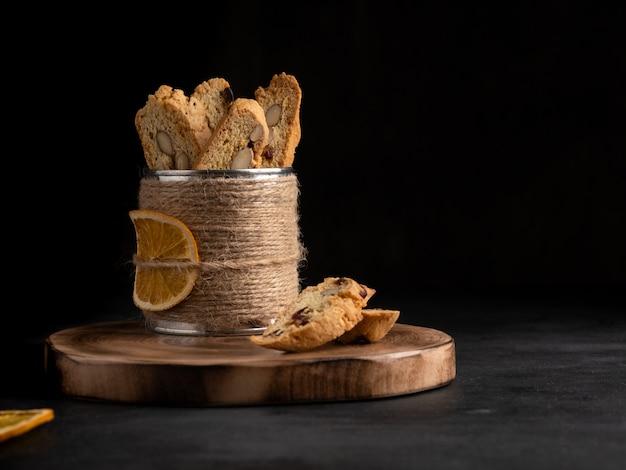 Cantucci (włoskie podwójne ciasteczka, biscotti) ze skórką pomarańczową, orzechami migdałów i suszoną żurawiną na drewnianym pokładzie, deska do krojenia. ciemne tło