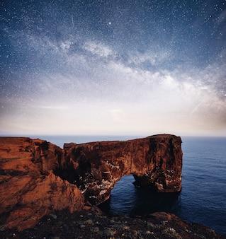 Cape dyrholaey w południowej islandii. wibrujące nocne niebo z gwiazdami, mgławicą i galaktyką. astrofotografia z głębokiego nieba