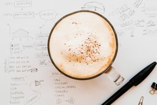 Cappuccino filiżanka w środku biznes planu papier