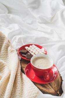 Cappuccino i czekolada na łóżku z plaid.