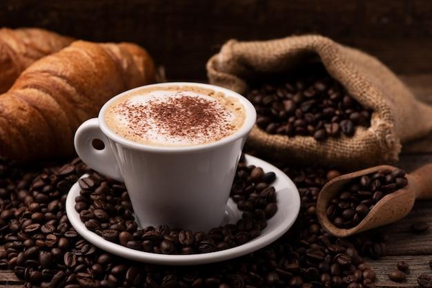 Cappuccino i rogalik z ziarnami kawy z bliska