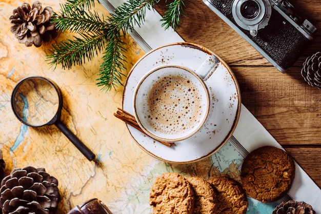 Cappuccino na drewnianym stole, mapa turystyczna i aparat.