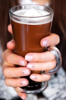 Cappuccino przez kieliszek trzymany przez kobietę.