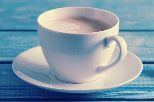 Cappuccino w białym kubku na niebieskim stole
