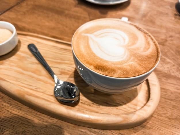 Cappuccino w ceramicznej filiżance na drewnianej tacy
