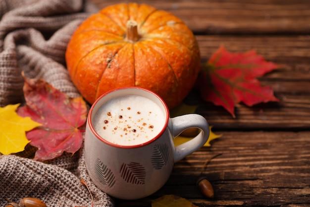 Cappuccino z dyni na drewnianym stole z jesiennym wystrojem