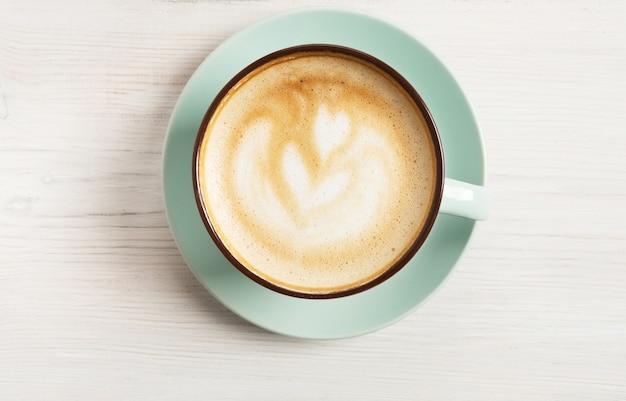 Cappuccino z pianką, niebieska filiżanka kawy zbliżenie widok z góry na białym drewnianym stole. kawiarnia i bar, koncepcja sztuki baristy.