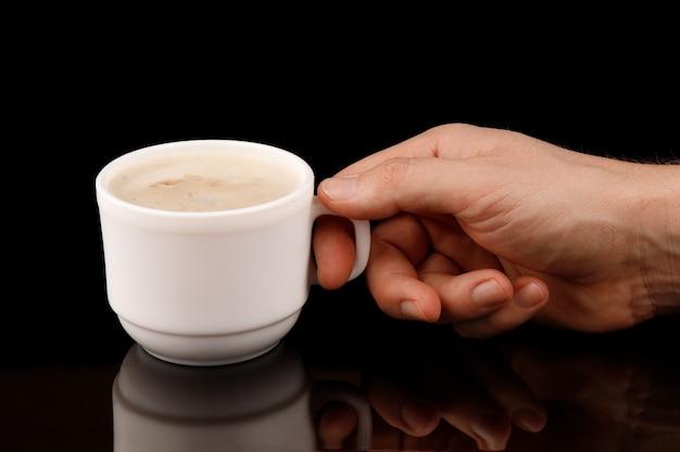 Cappuccino z pianką w filiżance w dłoni