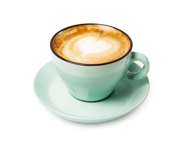 Cappuccino z pianką w kształcie serca, niebieski kubek kawy zbliżenie na białym tle. kawiarnia i bar, koncepcja sztuki baristy.