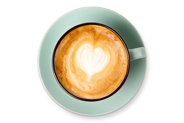 Cappuccino z pianką w kształcie serca w kształcie serca, niebieski kubek kawy zbliżenie widok z góry na białym tle. kawiarnia i bar, koncepcja sztuki baristy.