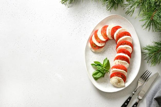 Caprese candy cane świąteczna przekąska na boże narodzenie serwowane na białym stole