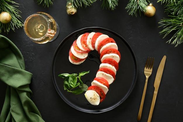 Caprese candy cane świąteczna przekąska na boże narodzenie serwowane na czarnym stole
