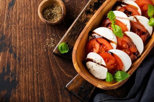 Caprese tradycyjna włoska sałatka w drewnianej misce z oliwek na starej rustykalnej powierzchni