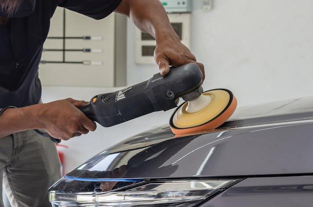 Car detailing - mężczyzna mechanik trzymający maszynę do polerowania samochodów. przemysł samochodowy, polerowanie samochodów oraz warsztat lakierniczy i naprawczy.