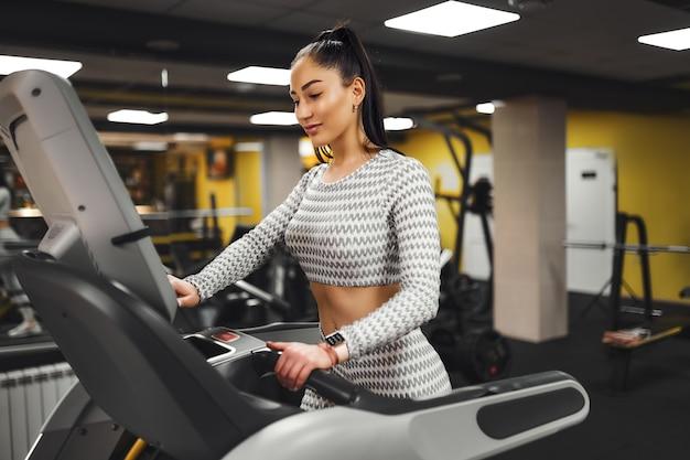 Cardio młoda kobieta zdrowa na bieżni na siłowni