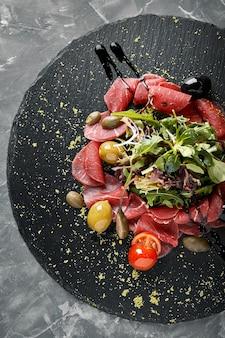 Carpaccio wołowe z rukolą na czarnym talerzu, tradycyjna kuchnia włoska