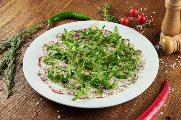 Carpaccio z cielęciny z parmezanem, rukolą i olejem truflowym na białym talerzu w kompozycji z przyprawami na drewnianej powierzchni kuchnia włoska
