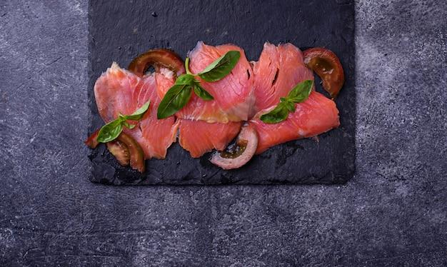Carpaccio z łososia z bazylią i pomidorem. selektywne skupienie