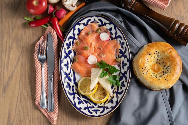 Carpaccio z łososia z kaparami, rzodkiewką i cytryną na talerzu z tradycyjnym uzbeckim
