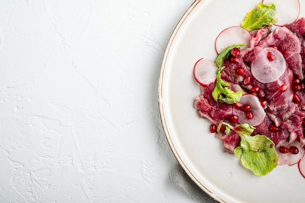 Carpaccio z marmurkowej wołowiny, z rzodkiewką i granatem, na talerzu, na białym kamiennym stole, widok z góry na płasko