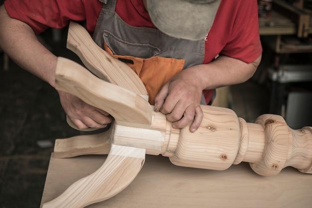 Carpenter tworzy stół z rzeźbionymi nogami