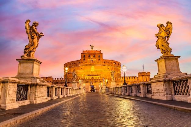 Castel sant'angelo i most sant'angelo podczas zmierzchu zachodu słońca w rzymie, włochy.