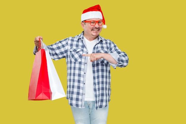 Casual stylem zabawny mężczyzna w średnim wieku w czerwonej czapce santa nowy rok, okulary stojące i wskazując palcem na torby na zakupy i toothy uśmiech, patrząc na kamery. studio strzał, odizolowane na żółtym tle