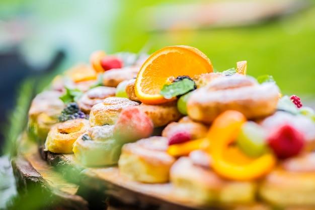 Catering w formie bufetu jedzenie na świeżym powietrzu ciasta kolorowe świeże owoce jagody pomarańcze i zioła dekoracje
