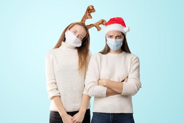 Caucasiam młode kobiety noszące medyczną maskę z santa hat i reniferem.
