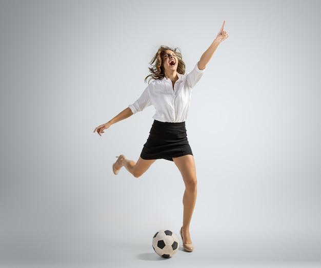 Caucasion kobieta w biurze ubrania kopie piłkę na białym tle na szarej ścianie