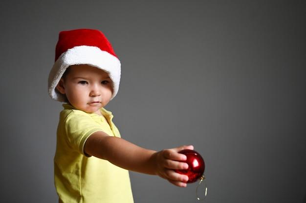 Caucasion mały chłopiec w santa hat boże narodzenie trzyma czerwoną piłkę christmas